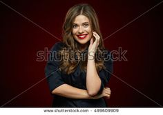 Toothy smiling woman portrait against dark red background. Curly hair.