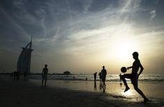 People enjoy Umm Suqeim Beach near the luxury Burj Al Arab Hotel on April 17, 2014 in Dubai, United Arab Emirates.