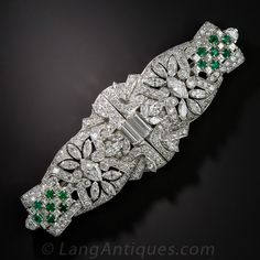 Art Deco Platinum Diamond and Emerald Clips. Fabulous Art Deco clips, masterfully hand crafted in platinum and extravagantly designed with over 10 carats of sparkling white diamonds and one carat of bright green emeralds. The elaborate mirror image design features a pair principal marquise-cut diamonds, each centering a pierced floral and ribbon motif set with smaller marquise and European-cut diamonds...