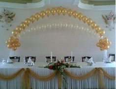 Double String of Pearls balloon arch over wedding head table.