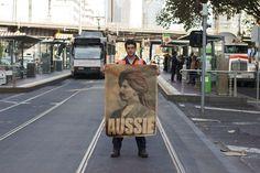 Peter Drew kadulla posterin kanssa. Katutaiteilja Peter Drew haluaa tehdä Australian unohdetuista muslimisiirtolaisista tunnettuja.