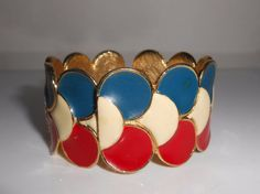 1970s Geneva Hidden Watch Ladies Enamel Bangle Bracelet 17 Jewels. There is a manufacture flaw on the back of the band as seen in the last picture. Not terribly noticeable but it is there. Red white and blue enamel over gold tone metal measuring 2 1/4 across the opening and 1 1/4 wide. Some light wear. Watch is in good working condition.