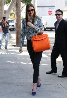 Miranda Kerr est arrivée à une réunion à West Hollywood portant une blouse Stella McCartney imprimée bleue et verte avec des jeans recouverts de noir, des pompes au cobalt et un sac orange Alexander McQueen.