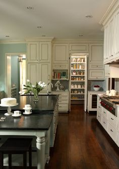 LOVE this kitchen... color, style.  Look at the pantry behind the wall of cabinets.  Cool!  Marble countertops on perimeter--gotta have 'em