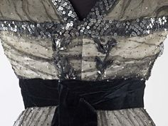 """1909-10 Dress. Museum of London. This skirt is part of a dress that is included in Janet Arnold's 'Patterns of Fashion: Englishwomen's dresses and their construction c. 1860-1940' (pages 58-59). Arnold describes it as 'an evening dress in black silk net covered with tiny 1/8"""" silver sequins over an ivory satin underskirt.'"""