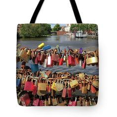 Locks Of Love Tote Bag by Marina Usmanskaya for home design.   The tote bag is machine washable, available in three different sizes, and includes a black strap for easy carrying on your shoulder.  All totes are available for worldwide shipping and include a money-back guarantee. The bridge over the river Trave in Lübeck, connecting the old Gothic town with the new part is the favorite place of the newlyweds.