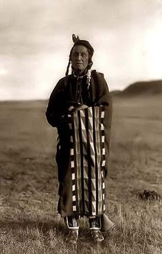 Here we present a dramatic image of Hidatsa Man. It was taken in 1908 by Edward S. Curtis.    The image shows a Hidatsa Indian posed, standing, full-length, draped with blanket, facing front; with mountain in background.    We have created this collection of images primarily to serve as an easy to access educational tool. Contact curator@old-picture.com.