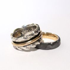 These wedding rings have been partly created from the customers own used gold, partly from new silver and is a great example of a pair with two very different rings.  His wedding band holds the original on the inside, while hers sports the original as a narrow and movable band on the outside.  Read more about the creation of these OOAK wedding rings at my blog: http://castensjewellery.blogspot.com/2010/11/reforging-wedding-rings.html
