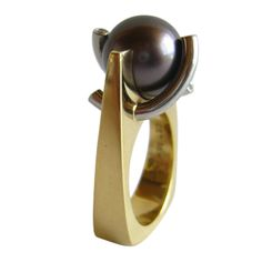 An 18k gold, platinum, diamond and Tahitan pearl ring, circa 1990s. Ring features an 11.9 mm South Sea black pearl and four small faceted diamonds set within curved platinum rods and an 18k gold setting. A finger size 5 3/4 and signed C & T, PLAT, 18K. In excellent original condition.