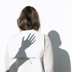 Play with another model's shadow, no face, other model is no in photo. R E A C H
