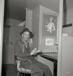 """March 1943. """"Conductor G. Reynolds, checking his waybills in a caboose of the Atchison, Topeka & Santa Fe Railroad between Argentine and Emporia, Kansas."""" Photo by Jack Delano for the Office of War Information."""