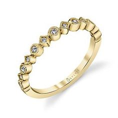 This unique yellow gold wedding band features mixed shapes of circles and triangles with different sizes of round brilliant diamonds in bezel settings with milgrain accents.  An intriguing combination of designs, the band can be used as a trendsetting wedding band or as a fashion statement of one's own personality when stacked with multiple bands of various metal colors and stones. The total weight is 0.15 carats.