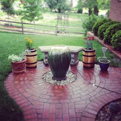 A water fountain, a bench, and flower pots make for an inviting front walkway