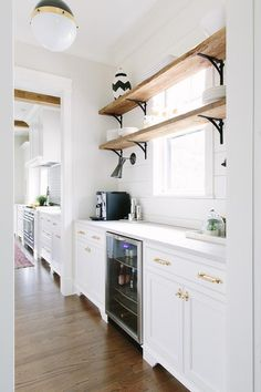 White shaker cabinets fitted with white quartz countertops and polished brass cabinet pulls hold a glass front beverage fridge and is sat under a window framed by a white shiplap backspash.