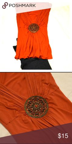 Orange fashion bejeweled sleeveless Orange sleeveless shirt with large bejeweled broach in center. No tag. Fits like a medium. Fantastic for a night out! unknown Tops Tees - Short Sleeve