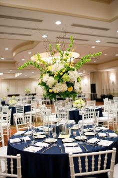 Tall centerpieces full of white and mini green hydrangea, lemon leaf, yellow roses and spray roses, and sprouting curly willow, bells of Ireland and oncidium orchids via Kate Parker Design