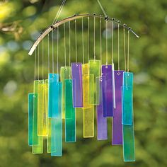 """Prism Chimes  Inspired by the beauty and colors of a prism, our chimes are created with cut glass panels in shades of blue, green, yellow, and purple that create a light, tranquil harmony of chimes in the wind and catch the sunshine with gorgeous color combinations when overlapping. Also looks wonderful indoors in a sunny window! Glass panels are hung with heavy nylon cording from a metal arch. Metal hanging cord and hook included. Measures 12-1/2"""" wide x 14-1/2"""" long."""