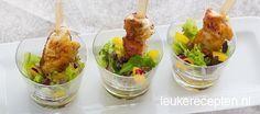Kleine kipspiesjes gemarineerd in en honing mosterd marinade geserveerd in een glaasje met salade