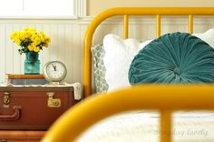 iron bed frame- love this yellow with the teal. LOVE the velvet pillow and suitcases by the bed. Decor, Headboards For Beds, Home, Home Bedroom, Bed, Painted Bed Frames, Bed Frame, Iron Bed, Yellow Bedding