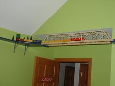 model train running along the ceiling from room to room.