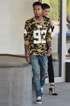 Tyga wearing  Bathing Ape London 1st Camo Mesh Football Long Sleeve, Cartier 18 Carat Yellow Gold And Diamond Love Bracelet , Rolex Day-Date II Yellow Gold Black Wave Arabic Dial Diamond Bezel President Band