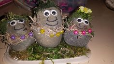 These are my homemade trolls from the movie! Found some river rock and hot glued them together.  Went to dollar tree and bought the Googly eye packs and the assorted moss. Took brown string and knotted four beads and tied it around. Last I grabbed an old Tupper ware lid and glued more of the moss down. I put some little rocks on the back that you can't see in this photo. But you can see in other photos.