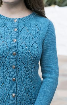 Analeigh cardigan is worked in one piece from top to bottom. The torso is shaped gently at the waist. Stitches for stockinette sleeves are picked up along armholes and caps are worked using a German short-row technique. The cardigan is embellished front and back with lace/cable pattern, which can be worked either from charts or from written descriptions.