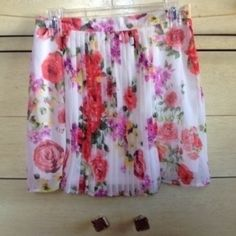 """White Floral Mini Skirt Okay so the tag says L,  BUT on nasty gal it was sent as a M and fits as such maybe even a small. I'm 5'6"""" it's a little short on me There are pleats at center front  Zipper closure Reasonable offers welcomed  14"""" at the waist 15.75"""" long Nasty Gal Skirts Mini"""