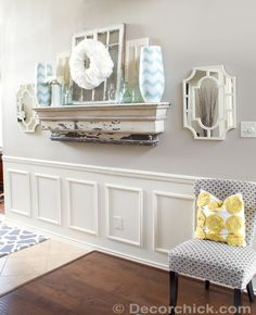 Use a chair rail, wooden frames, caulking, and several coats of white paint to create this wainscoting look-alike.