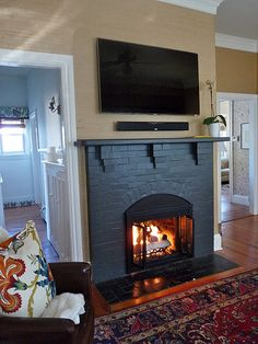I really, really like brick fireplaces painted dark grey - so smart because it is easy to keep clean