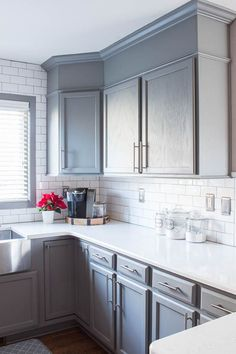 A builder grade kitchen gets a new look with classic features like gray cabinets, Quartz counters and subway tile. Beautiful makeover!