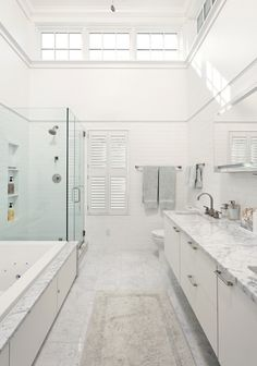 carrera marble bathrooms subway tiles drop in tub undermount cabinets countertops two piece toilet glass door alcove shower white walls sink contemporary design of Fabulous Carrera Marble Bathrooms to be Awestruck By