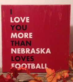 """Wall Sign, Husker Football Sign, Cornhuskers Wall Sign, University of Nebraska Rustic Sign, I Love You Sign, Cornhuskers Wall Decor. This distressed wooden sign is 12"""" x 12"""" in size*. It has a red background with black and white lettering. Great for the Nebraska Football fan. This sign has a red back with a saw tooth hanger and is finished with a satin poly coat. * Measurements are an approximation."""
