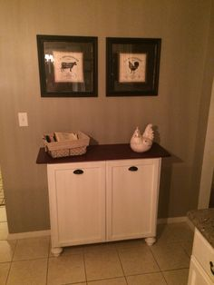 DIY Double tilt out trash can- made with unfinished wall cabinet from Home Depot, furniture feet painted white, finished with left over bead board on the sides, an old console table top) could stain a new piece of wood for top)