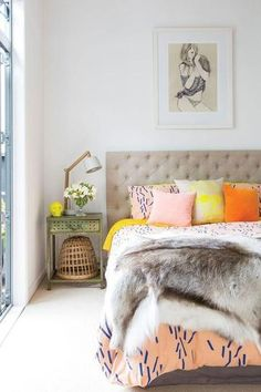 25 gorgeous bedroom decorating ideas - lovely mix of bright pillows in warm colors, mixed with a fur throw, shabby chic nightstand decorated with a modern desk lamp and flowers, + feminine framed illustration