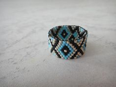 Beaded ring with miyuki delica seed beads that will add an enthic touch to your outfits.  The pattern is created by the careful allignment of light blue, black and silver (silver galvanized, duracoat) beads. This ring is impressive from every angle and will add a special touch to your ootd.  For custom orders on ring sizes, do not hesitate to contact us and we will do our best to facilitate your request. Regarding ring sizes, you can advise the following site: http://www.ringsizes.c...