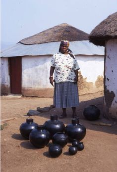 Africa | Nesta Nala (1940 - 2005) outside of her homestead with some of her traditional Zulu beer pots. The ukhamba -a smoke-black, thin-walled, round bottomed beer pot is still used in ceremonies by the Zulu-speaking people of South Africa. Thembi and Jabu Nala, the daughters of Nesta Nala, follow in their mother's footsteps by developing their pots for the urban craft gallery and collector market. | Image ©M. Vincentelli.