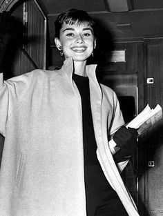 """The actress Audrey Hepburn photographed during her arrival at the Idlewild Airport (opened as """"New York International Airport"""" in 1948, it was commonly known as """"Idlewild Airport"""", before being renamed in 1963 as """"John F. Kennedy International Airport"""", in memory of John F. Kennedy, 35th President of the United States, following his assassination) in New York City, New York (USA), from Los Angeles, California (USA), on December 13, 1953.Audrey was wearing:Coat: Claire McCardell (of wool in a…"""
