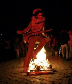 An Iranian woman jumps over a bonfire, in the Pardisan Park in Tehran during Chaharshanbe Souri, or Wednesday Feast. Chaharshanbe Soori is the ancient Festival of Fire celebrated on the eve of the last Wednesday of the Iranian year. Iranians jump over burning bonfires while throwing firecrackers to celebrate arrival of spring and the upcoming holiday of Nowruz.