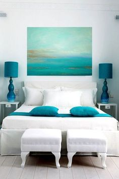 See 25 gorgeous beach house interior inspirations: All white with turquoise pillows art and side lamps.