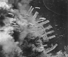 Incendiary bombs are dropped from B-29 Superfortresses of the U.S. Army Air Forces on already-burning landing piers and surrounding buildings in Kobe, Japan, on June 4, 1945. (USAF)