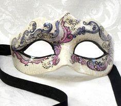 Maschera Perla Viola OR06 realizzata completamente a mano in cartapesta con l'aggiunta dello screpolato (Craquelè). Pezzo Unico.Le decorazioni, anch'esse realizzate a mano, sono in colori acrilici e di alto livello dal punto...