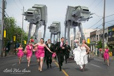 Toronto, Ontario-based Little Blue Lemon Photography recently created a geektastic wedding photo showing a terrified bridal party being chased through the streets by an angry mob of AT-AT Walkers (Star Wars). They used photos taken of a toy AT-AT Walker and their impressive Photoshop skills to end up with this final result.   http://laughingsquid.com/bridal-party-being-chased-through-the-streets-by-angry-mob-of-at-at-walkers/