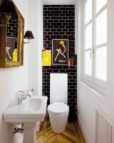 Un aménagement de WC bien pensé pour compenser le manque de largeur. Le carrelage noir sur le mur de la cuvette par un effet de contraste augmente l'impression d'espace au coté des murs peints en blanc. Le parquet se charge d'ajouter un sentiment de confort à la déco de ces WC noir et blanc.