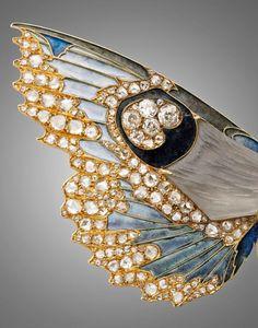 René Lalique, Rare et importante broche-pendentif devant de corsage (détail) en or jaune stylisée de deux papillons de nuit en vol, les corps en pâte de verre grise moulée au naturel, les ailes émaillées polychromes en pique-à-jour et serties de diamants taillées en rose et à l'ancienne. Photo Artcurial