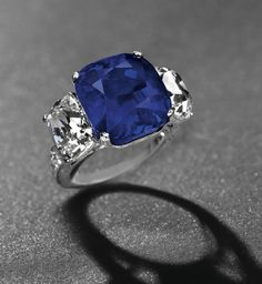 cushion-shaped sapphire, weighing approximately 19.88 carats, flanked on either side with cushion-shaped diamonds, weighing approximately 3.02 carats each; graduated diamond line shoulders and engraved sides
