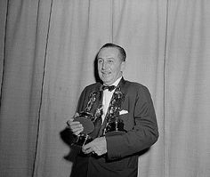 Walt Disney holding four Oscars 1954