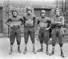 Photograph of four members of the 1920 St. Thomas College football team. From left to right, Leonard McGovern, James Eagen, Dan McDevitt, and Nicholas Helring. Taken in front of Old Main.