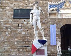 """FIRENZE. Una fascia nera al braccio e una bandiera francese ai piedi. La riproduzione del David di Michelangelo all'ingresso di Palazzo Vecchio in piazza della Signoria a Firenze """"vestita"""" a lutto per la strage al quotidiano satirico Charlie Hebdo di ieri a Parigi."""