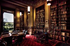 Gentleman's library with dark wood finishes, antique gold walls and regal red carpet.